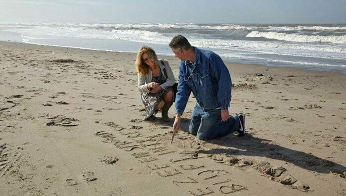 Mensen op het strand die een tekst in het zand schrijven